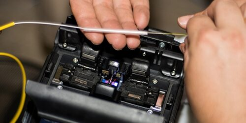 Fiber optic cable splicing by engineer with Optical Fiber Fusion Splicer instrument professional machine. Close up, selective focus. Modern and fast internet and network concept